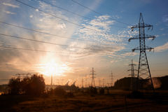 High-voltage transmission towers in suburbs. At sunrise Stock Images