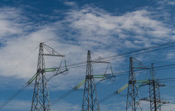 High-voltage transmisson line against the blue sky. Four electrical pylons in a row Royalty Free Stock Photos