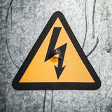 High voltage triangle sign on gray metal wall Stock Photos
