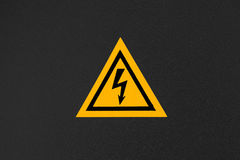 High voltage triangle warning sign mounted on black Stock Photo