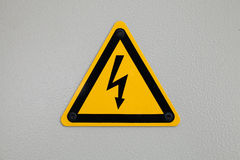 High voltage triangle warning sign mounted on gray Stock Photography