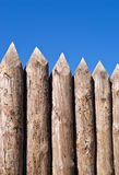 High wall of old wooden sharpe. Ned logs over blue sky Royalty Free Stock Photo