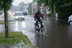 High water after downpour. ENSCHEDE, NETHERLANDS - JUNE 06: A man on a bicycle is struggling through the high water in the streets after a downpour, JUNE 06 Stock Image