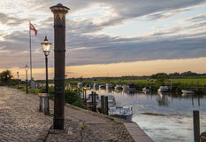 Sunset over the harbor of Ribe with the high water mark column in the front, Denmark Stock Photography