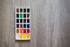 High water watercolor paints on the wooden background. Royalty Free Stock Photo