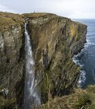 High waterfall at the edge of cliffs