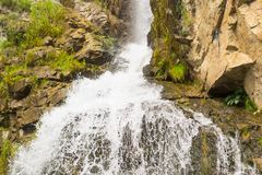 A high waterfall in the mountains of the Altai with sprinkled dr royalty free stock images
