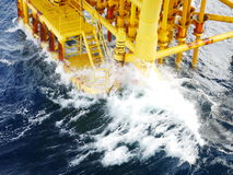 High wave hitting the Boat Landing and Producing Slots at Offshore Platform. During bad weather conditions (high wave) - Oil and Gas Industry Stock Photo