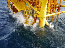 High wave hitting the Boat Landing and Producing Slots. At Offshore Platform during bad weather conditions (high wave) - Oil and Gas Industry Stock Images