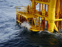 High wave hitting the Boat Landing and Producing Slots. At Offshore Platform during bad weather conditions (high wave) - Oil and Gas Industry Stock Image