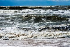 High wave in a storm, tsunami, flood. High wave in a storm is broken against a sandy beach Stock Photo