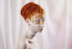 Beautiful girl with red hair. High wedding hairstyle in the Greek style. Vogue style portrait of a girl with a red white and golden bodyart on her face. Body Stock Photography