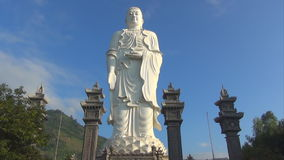 High white Buddha stands on a background of blue sky. clouds race across the sky. Timelapse. stock footage