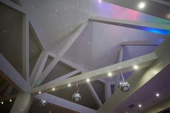 The high white ceiling with exposed beams. Decorated with disco balls.With the backlight. Night life. The high white ceiling with exposed beams. Decorated with Royalty Free Stock Image
