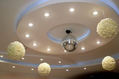 The high white ceiling with exposed beams. Decorated with disco balls.With the backlight. Night life stock photography