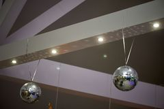 The high white ceiling with exposed beams. Decorated with disco balls.With the backlight. Night life. The high white ceiling with exposed beams. Decorated with Stock Image