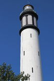 High of a white lighthouse on a background of cloudless blue sky Stock Image