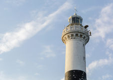 High white stone lighthouse against a blue evening sky with clouds Stock Photo
