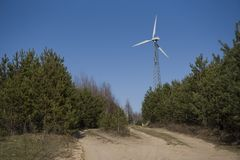 High windmill on the edge of the forest. High wind turbine generator in the forestn stock image