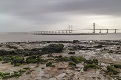 High winds low tied in the Severn Estuary. Fast moving clouds over The Second Severn Bridge Boarder Crossing, Low tied exposing mud and rock flats Stock Photos