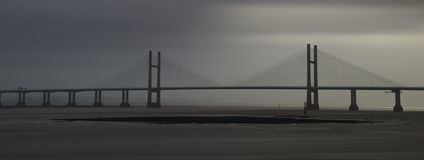 High winds the Severn Estuary. Fast moving clouds over The Second Severn Bridge Boarder Crossing, Low tied exposing mud and rock flats Royalty Free Stock Image