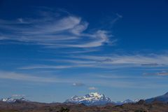 High wispy cirrus clouds filling the blue sky in Patagonia. With a glacier covered peak in the foreground. High wispy cirrus clouds filling the blue sky in Stock Photos