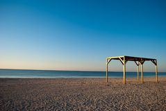 Wooden canopy awning gazebo by the sea beach sand morning. High wooden canopy awning arbor deserted beach early in the morning shore of the sea calm blue clear Royalty Free Stock Image