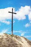 High wooden cross on the hill. High wooden cross stands on a sandy hill on a background of the cloudy sky Royalty Free Stock Images