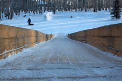 High wooden ice slide with steep slope and icy frozen sliding surface stock images