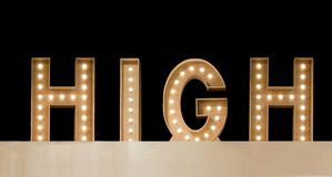 High. Wooden illuminated letters spelling HIGH Stock Image