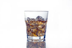 Highball glass of scotch. Back-lit glass of whiskey or scotch on reflective surface Royalty Free Stock Photo