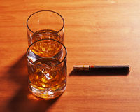 Highball whiskey glass with ice and cigar on wooden background. Royalty Free Stock Photo