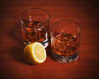 Highball whiskey glass with ice and lemon. Stock Photos