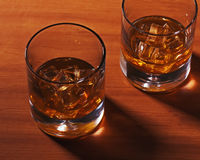 Highball whiskey glass with ice on wooden background. Royalty Free Stock Photo