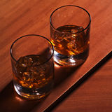 Highball whiskey glass with ice on wooden background. Royalty Free Stock Images