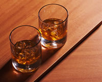 Highball whiskey glass with ice on wooden background. Stock Photos
