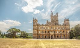 Highclere castle with park and green trees newbury England. Highclere castle amous as downton abbey with park and green lebanon cedar Neubury Hampshire England Royalty Free Stock Photography