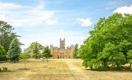 Highclere castle with park and green trees newbury England. Highclere castle famous as downton abbey with park and green trees newbury England Stock Photo