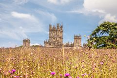 Highclere castle in summer with wildflowers meadow newbury Engla. Highclere castle famous as downton abbey with wildflowers meadow newbury England Royalty Free Stock Image