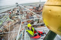 Highclimber worker man in the city, high church royalty free stock photography