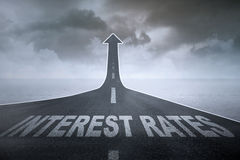 Higher Interest Rates. Concept: The words interest rates on a straight road turning into ascending arrow stock illustration