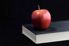 Higher learning. A red apple sits on an unopened black book.  This is a low key photo with a jet black background.  There is room for print/words Royalty Free Stock Photography