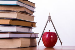 Higher school time. Pile of books with apple and compass on white background royalty free stock image