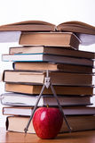 Higher school tools. Pile of books with apple and compass on white background stock photos