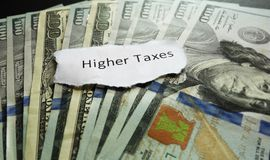 Higher Taxes. Note on assorted cash Royalty Free Stock Photography