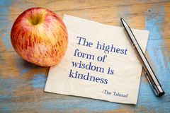The highest form of wisdom is kindness. Handwriting on a napkin with a fresh apple Royalty Free Stock Photos