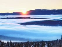 Highest hills above inverse mist. Winter cold weather in mountains. Colorful fog. Misty valley in winter mountains. Peaks of mountains above creamy mist royalty free stock photos