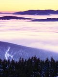 Highest hills above inverse mist. Winter cold weather in mountains. Colorful fog. Misty valley in winter mountains. Peaks of mountains above creamy mist stock photos