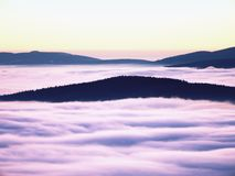 Highest hills above inverse mist. Winter cold weather in mountains. Colorful fog. Misty valley in winter mountains. Peaks of mountains above creamy mist royalty free stock photo