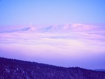 Highest hills above inverse mist. Winter cold weather in mountains. Far mountain peak with observatory above creamy mist. Shinning lights on antenna. Wavy fog in royalty free stock photography